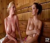 Twee rondborstige meisjes in een sauna