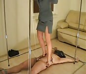 Frau trägt High Heels und trampelt auf ihrem Sklaven herum
