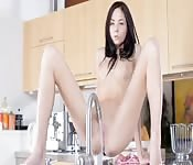 Horny brunette plays in the kitchen