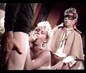 Eine Blondine und zwei maskierte Männer