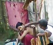 Mulher se lavando ao ar livre ganha ajuda de homem