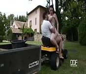 Geneukt op een schommel en een rijdende grasmaaier